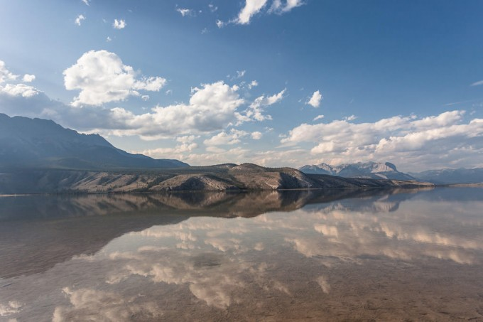Fluffy cumulus clouds are reflected in Jasper Lake on a warm late summer day in Jasper National Park, Alberta, Canada