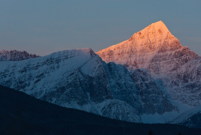The first rays of sunlight illuminate the southeast face of Mount Edith Cavell on a clear winter morning in Jasper National Park