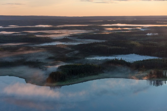 Mist rises from several small mirror smooth lakes in the early morning of a warm summer day in the boreal forest of northern Alberta, Canada