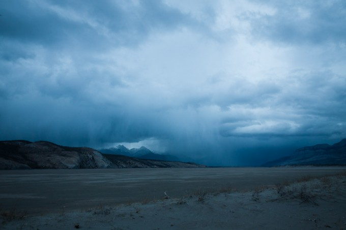 A late evening spring rain falls onto the dry lakebed of Jasper Lake at Devona Flats in Jasper National Park