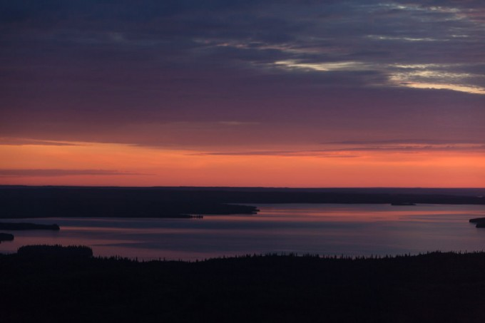 The sky glows orange and purple in the first light of dawn over Namur Lake. Taken from a helicopter over the boreal forest of northern Alberta, Canada