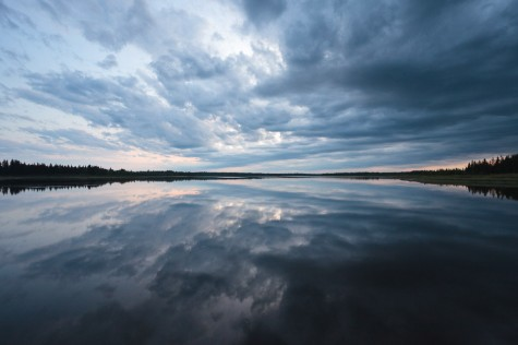 Low clouds loom at dusk over a glassy calm boreal lake